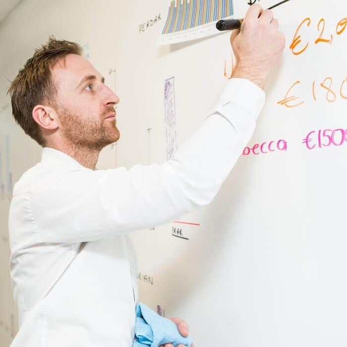 Man writing on wall painted with Smart Magnetic Whiteboard Paint White