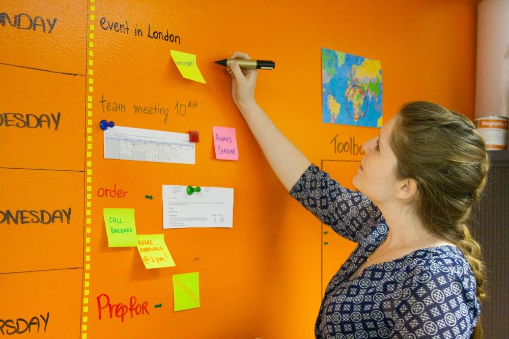 woman writing on magnetic-whiteboard-paint-wallclear