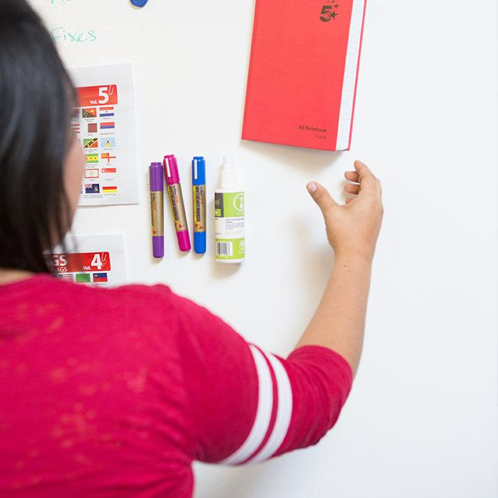 Woman-hanging-up-notebook-on-magnetic-wall-not-magnetic-boards