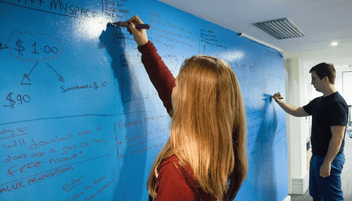 group of people writing on whiteboard wall turn your wall into a whiteboard