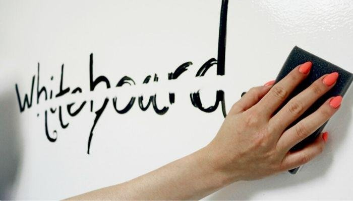 person-wiping-away-writing-on-dry-erase-paint