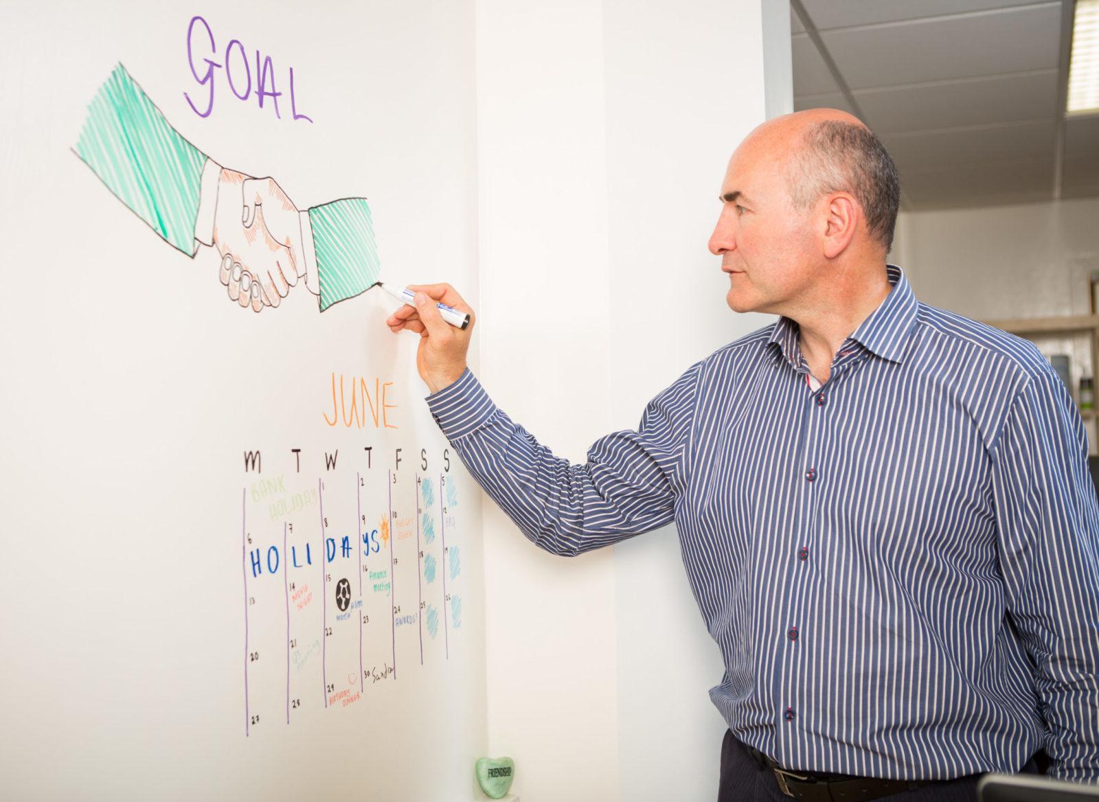 man using smart whiteboard paint wall in office